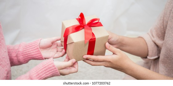 Close up hands giving gift box, girl surprise her mother with gift box. Boxing day holiday birthday christmas and mother's day concept banner