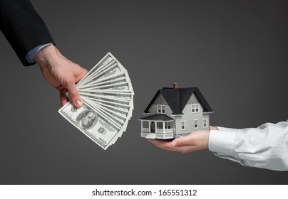 Close up of hands giving house model to other hands with money. Concept of real estate and deal