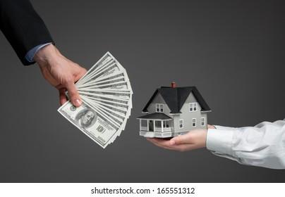 Nahaufnahme von Händen geben Haus Modell an andere Hände mit Geld. Konzept der Immobilien und Geschäfte