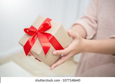 Close up hands giving surprise gift box. Boxing day holiday birthday Christmas mother's day concept.