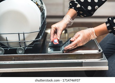 Close up of hands in gloves putting dishwasher tablet or soap detergent tablet into dishwasher box. Full dishwashing machine with plates