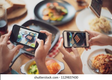Close up hands of group of woman taking food photo by mobile phone on wood table in restaurant.