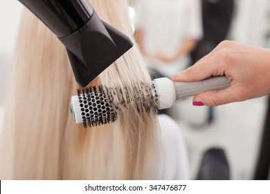 Close up of hands of hairdresser drying human hair with equipment. The woman is holding a comb