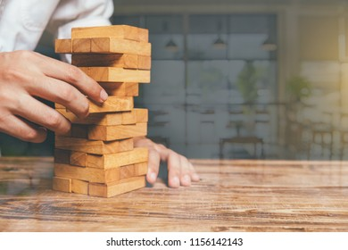 Close up of hands helping build,Planning, risk and strategy in business, businessman and engineer gambling placing wooden block on a tower,warm colours sun light at reflection glass