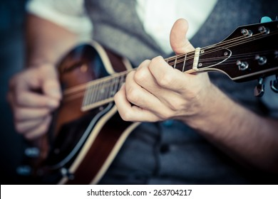 close up hands hipster man playing mandolin in the city - Shutterstock ID 263704217