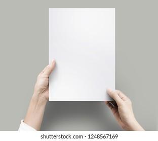 Nahaufnahme von Händen, die leeres Papier für die Arbeit am Schreibtisch Büro Draufsicht halten. Beschneidungspfad einzeln.