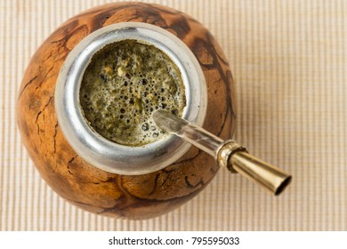 close up of the hands holding the calabash (gourd) with yerba mate drink, top view, freshly made, hot ethnic drink.