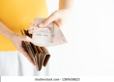 close up hands holding cash and open brown leather wallet. Left hand is pulling Thailand money (Baht)and right hand holding wallet.