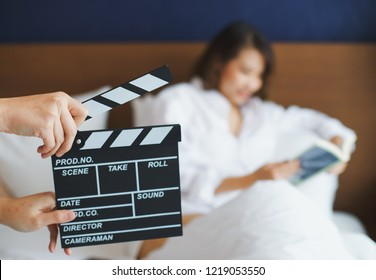 Close up hands holding clapperboard during the production of the film with asian woman reading a book in the scene
