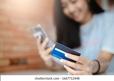 Close up hands holding credit card and using mobile smart phone outdoor, Online shopping, woman happy.(credid card mockup)