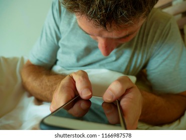 close up hands holding mobile phone of young man at home bedroom using internet social media app on smartphone networking and texting lying in bed in communications technology concept