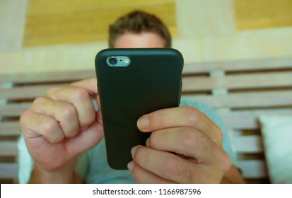 close up hands holding mobile phone of young man at home bedroom using internet social media app on smartphone networking and texting from bed in communications technology concept