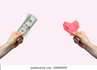 Close up hands holding money and paper heart. Sentimental value/ Valentine's day concept.