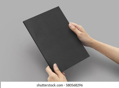 Close up hands holding Notebook black color a5 size on a grey background.