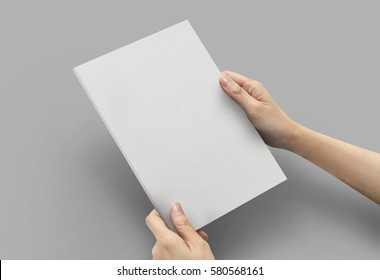 Close up hands holding Notebook white color a5 size on a grey background.