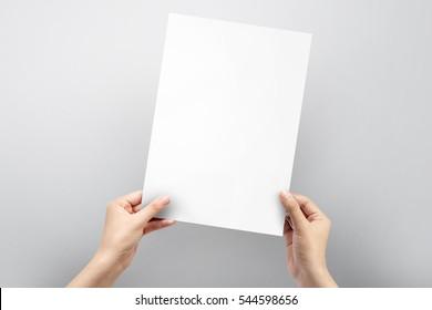 Lukk opp hendene som holder papir tomt a4-størrelse for brevpapir på en grå bakgrunn.