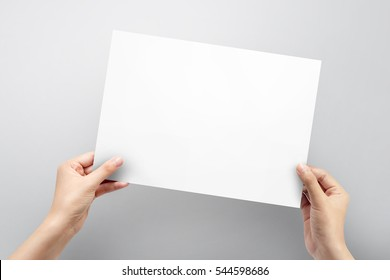 Close up hands holding paper blank a4 size for letter paper on a grey background.