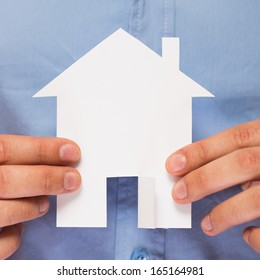 Close up of hands holding paper house in his hands