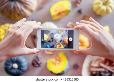 Close up of hands holding smartphone, taking photo of colorful vegetables on wooden table.