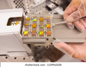 close up or Hands holding tweezers lead frame with a silicon wafer on surface for inspection from production in semiconductors manufacturing facility,  blurred background