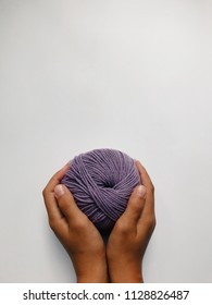 A close up of children's hands holding wool ball, purple yarn. Knitting concept, copy space, vertical photo