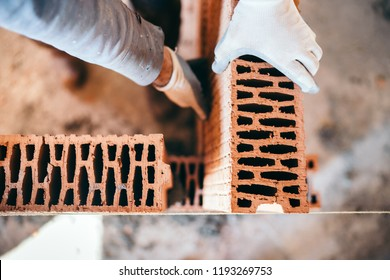 Close up hands of industrial male bricklayer installing bricks on construction site