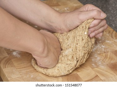 Close up of hands kneading wholemeal bread dough on a wooden board