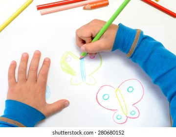 Close up of the hands of a little child drawing a butterfly with color pencils