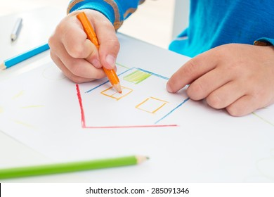 Close up of the hands of a little child drawing a house with color pencils