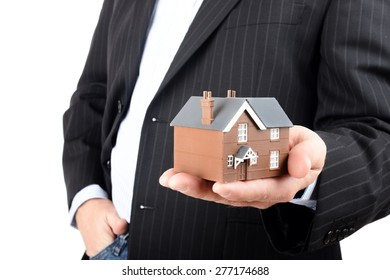 Close up of hands with little home. Concept of deal and real estate