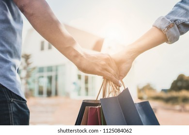 Close up hands of love couple holding shopping bag to home, concept as buying goods for new house