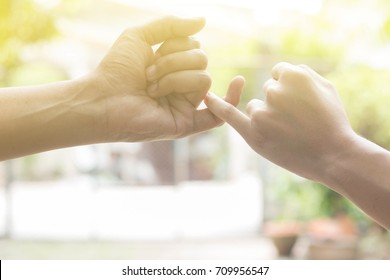 close up hands of lovely couple hooking each other's little finger together with copy space for text and soft light effect: pinky swear, pinkie promise concept
