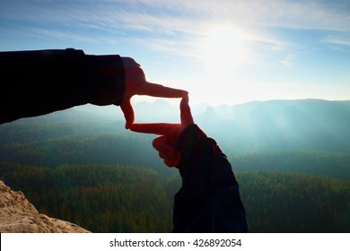 Close up  hands make frame gesture. Blue misty valley bellow rocky peak. Sunny spring daybreak in mountains.