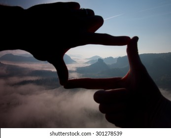 Close up of hands making frame gesture. Blue misty valley bellow rocky peak. Sunny spring daybreak in rocky mountains.