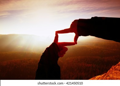 Close up hands making frame gesture. Orange misty valley bellow. Sunny spring daybreak in mountains. Red vintage style.