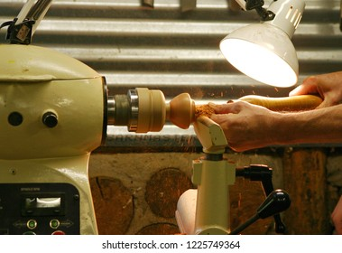 Close up of the hands of a male master woodturner turning a wooden bowl on a lathe