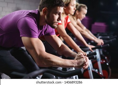 Close up hands of man biking in spinning class. Group of smiling friends at gym exercising on stationary bike. Happy cheerful athletes training on exercise bike.