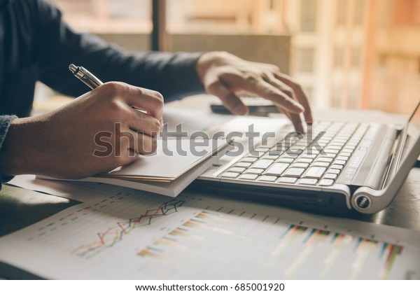 Close up hands man doing finances with using laptop and writing note at home office