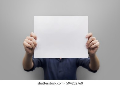 Close up hands man holding behind a paper blank for banner on gray background