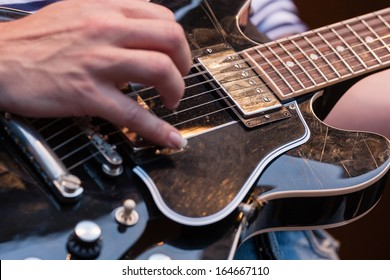 Close up of the hands of a man plucking the strings on a decorative wooden electric guitar with focus to the pickup and strings