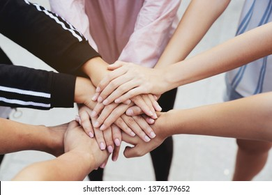 Close up at the hands many teenage girls. Show unity as a collaborative work together. To succeed, one has to understand each other in communication. Concept International Women's Day