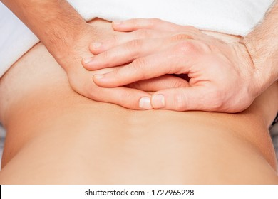 Close up of hands of massage therapist doing back massage on back of young man.