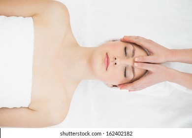 Close up of hands massaging a beautiful woman's forehead at beauty spa