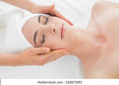 Close up of hands massaging a beautiful woman's face at beauty spa