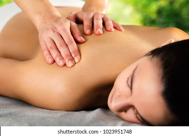 Close up of hands massaging female back and shoulder against green background.