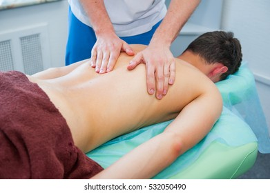 Close up hands of the masseur - young man's back during a session, massage studio