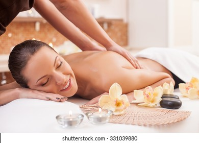 Close up of hands of masseuse massaging back of young lady. The beautiful woman is lying and relaxing. She is smiling. Her eyes are closed with relaxation