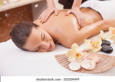 Close up of hands of masseuse massaging a young woman at spa. The girl is lying and smiling with relaxation. Her eyes are closed with pleasure