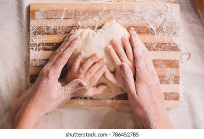 Close up  hands of mother and son kneading a dough on a wooden board