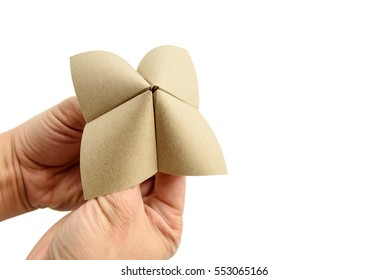 Close up of hands in a mulberry paper cootie catcher, a fortune teller (also called a chatterbox, salt cellar or whirlybird) is a form of origami used in children's game. Isolated on white background.